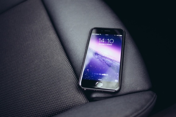 A black iPhone 6 with purple home screen on AMOLED display, pictured in Anthony Beyer's car.