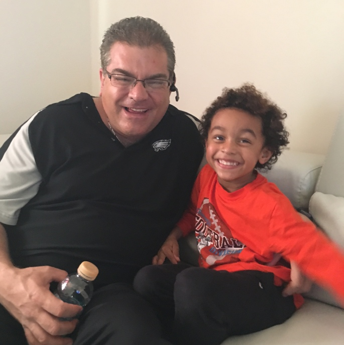 Anthony smiling from ear to ear, having a ball with his son.