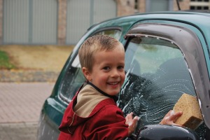 A young boy washing a car